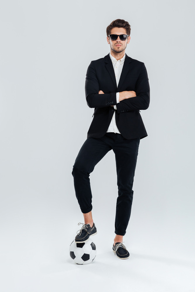 Full length portrait of a confident handsome man in sunglasses and black suit standing with arms crossed and with leg on the soccer ball over grey background