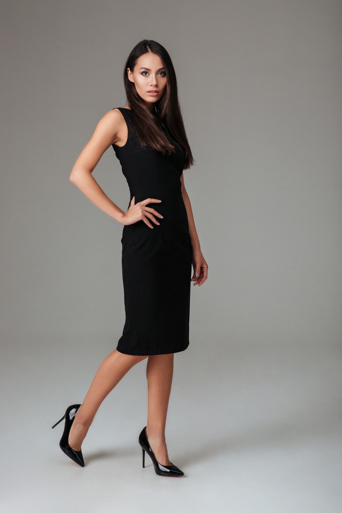 Full length portrait of a fashion young woman posing in black dress isolated on a gray background