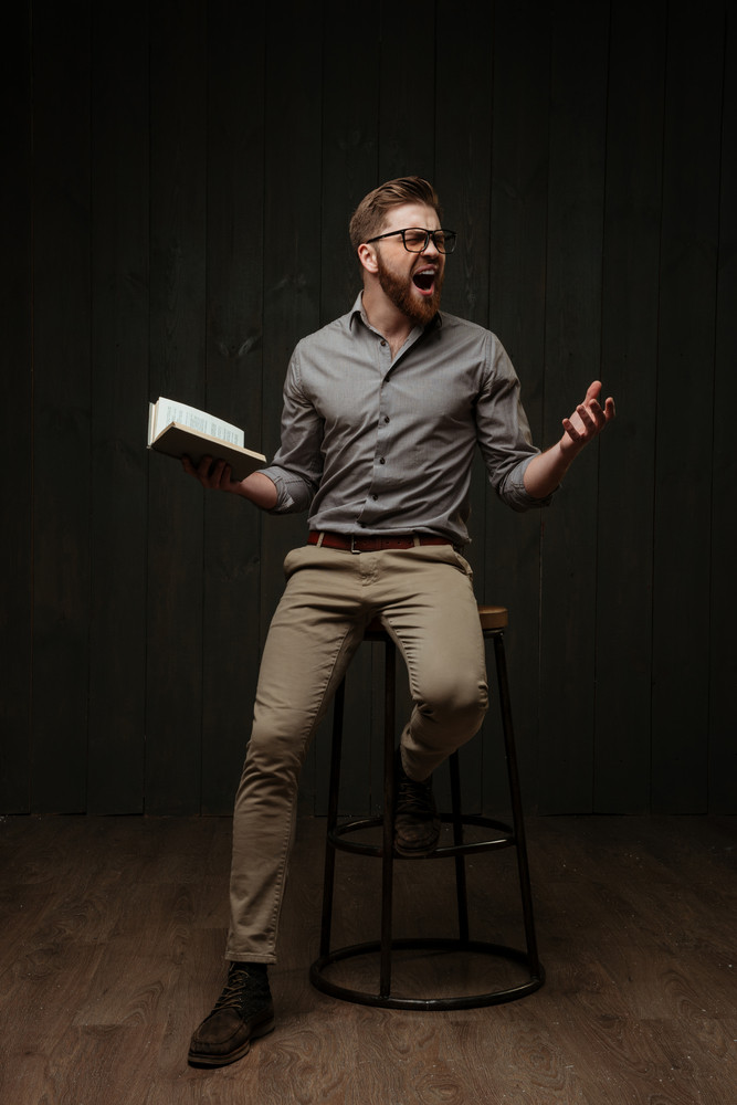 Full length portrait of a furious mad man in eyeglasses shouting while sitting on chair with book isolated on a black wooden background