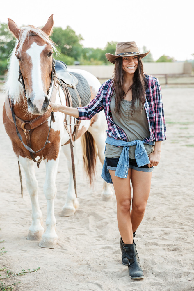 Full length portrait of a girl taking her horse for a walk at the farm