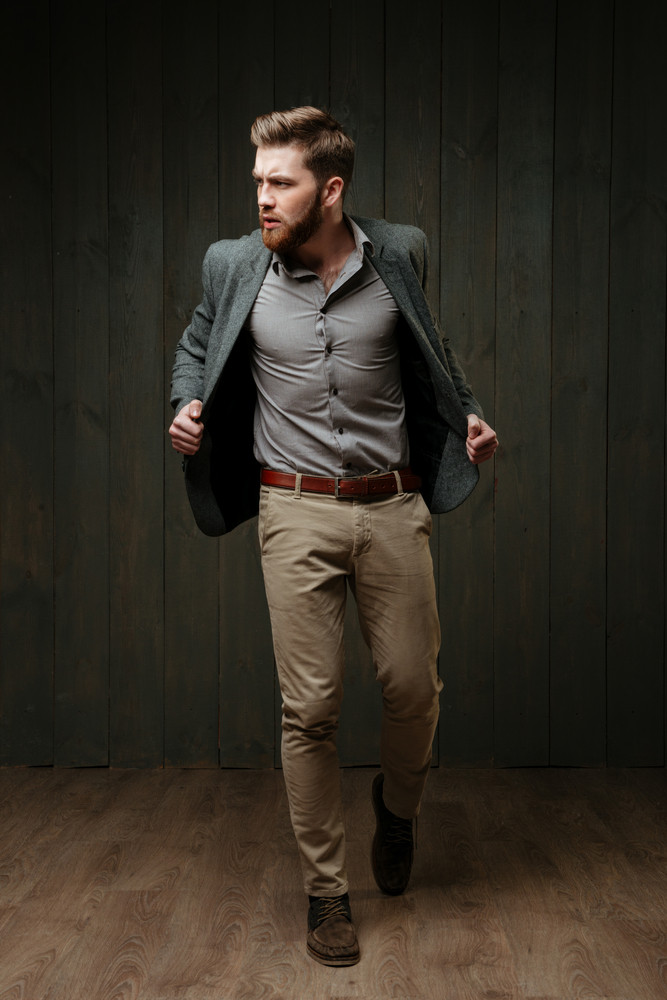 Full length portrait of a handsome stylish man in jacket standing and posing isolated on a black wooden background