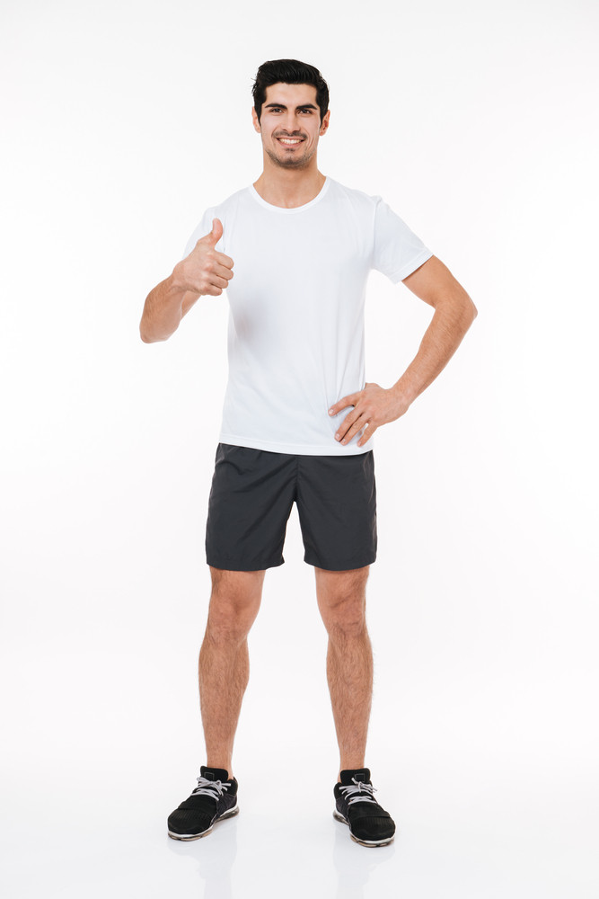 Full length portrait of a happy fitness man showing thumbs up isolated on a white background