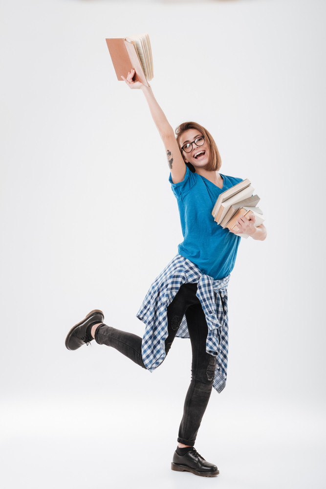 Full length portrait of a happy smiling female student holding book above her head isolated on the white background