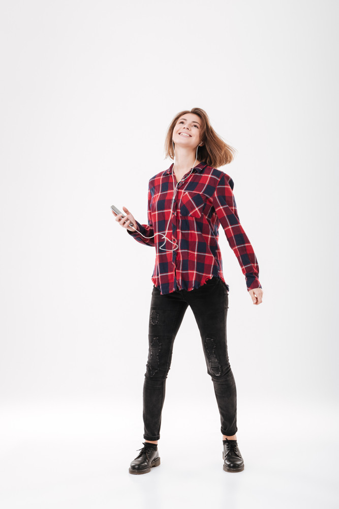 Full length portrait of a happy smiling girl in plaid shirt listening music with earphones over white background