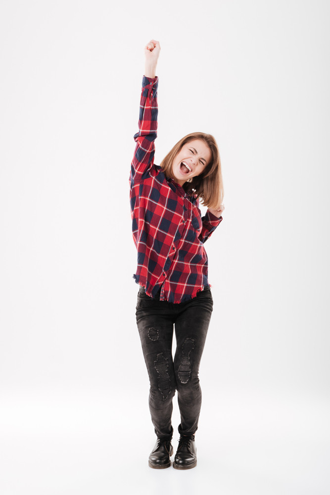 Full length portrait of a happy woman celebrating her success isolated on a white background