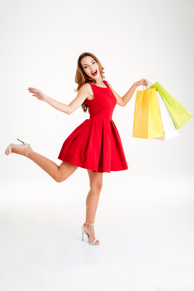 Full length portrait of a happy woman in red dress holding shopping bags isolated on a white background