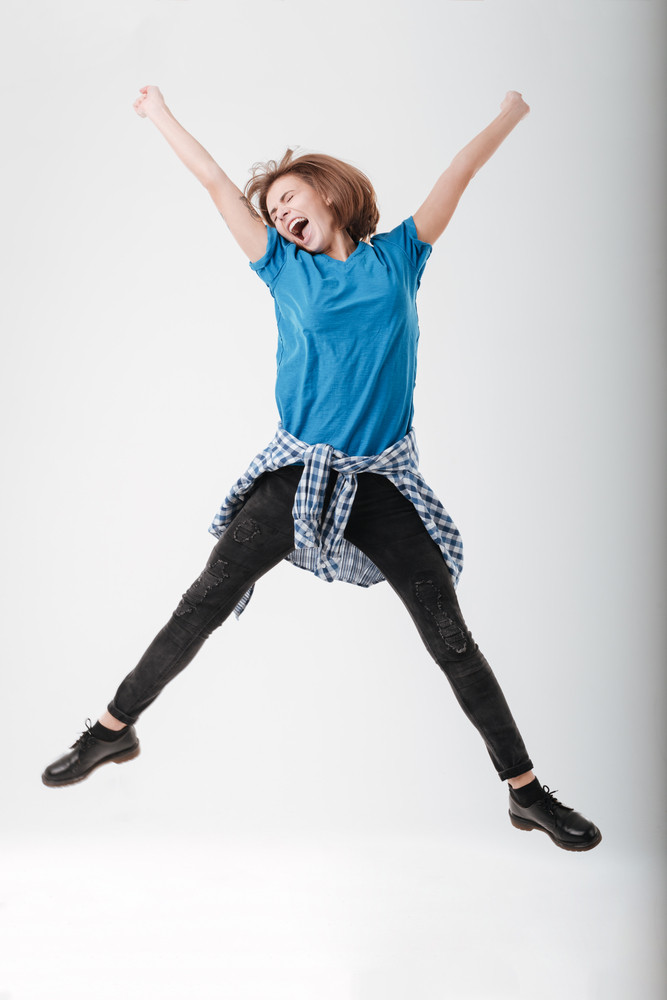 Full length portrait of a happy woman jumping isolated on a white background