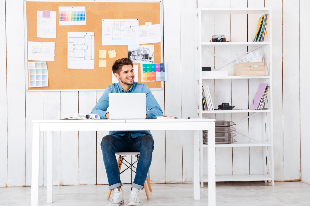 Full length portrait of a happy young handsome businessman using laptop computer in office