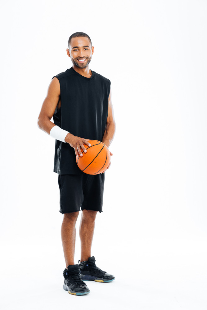 Full length portrait of a laughing young cheerful african man with basket ball isolated on a white background