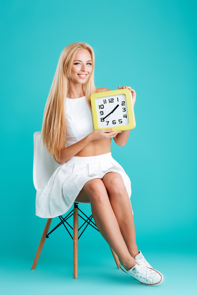 Full length portrait of a pretty smiling girl holding wall clock and sitting on chair isolated on the blue background