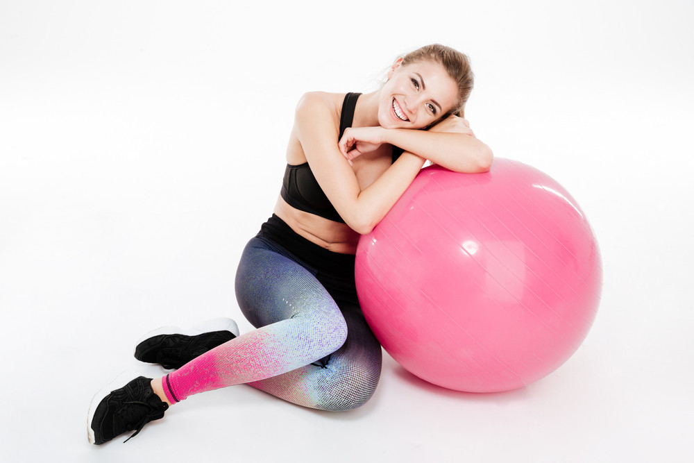 Full length portrait of a pretty sports woman relaxing on pink fitness ball isolated on white background