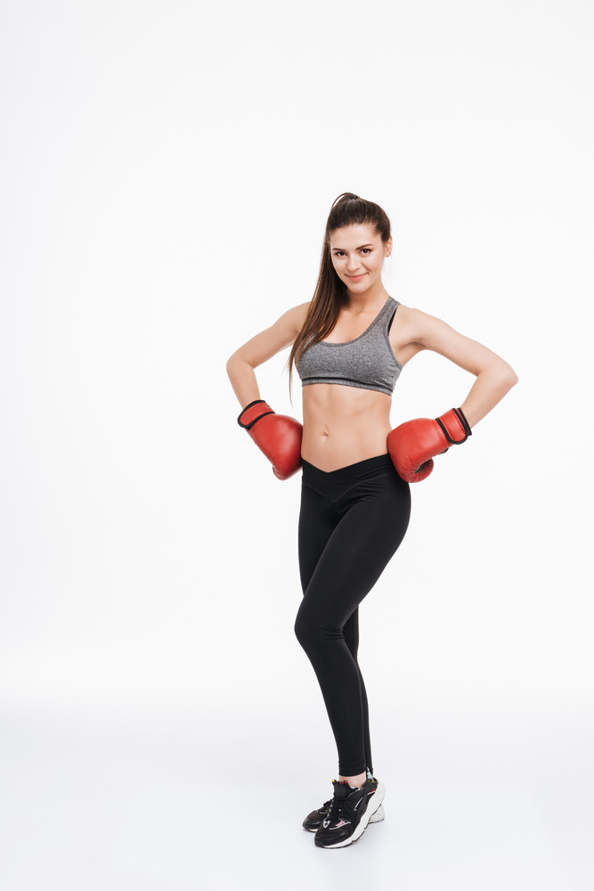 88df867d0a7a1 Full length portrait of a satisfied smiling fitness woman wearing boxing  gloves and standing with hands