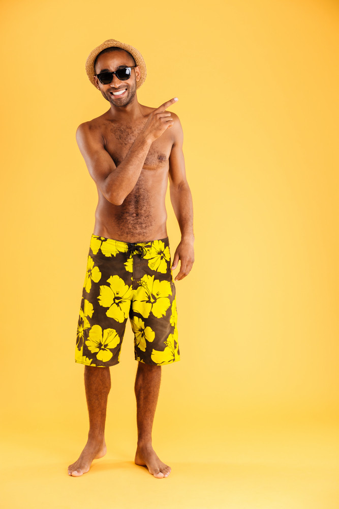 Full length portrait of a smiling afro american man in swimwear pointing finger away isolated on a orange background
