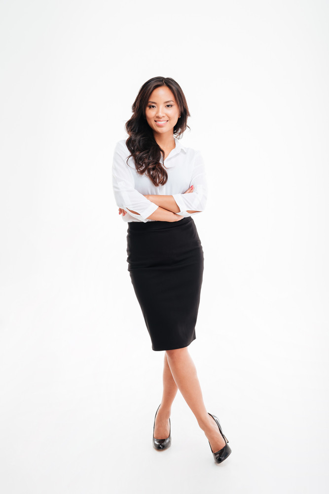 Full length portrait of a smiling asian businesswoman standing with arms folded and legs crossed isolated on a white background