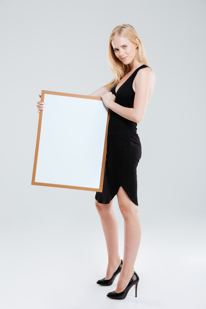 Full length portrait of a smiling beautiful woman holding blank board and looking at camera isolated on a white background