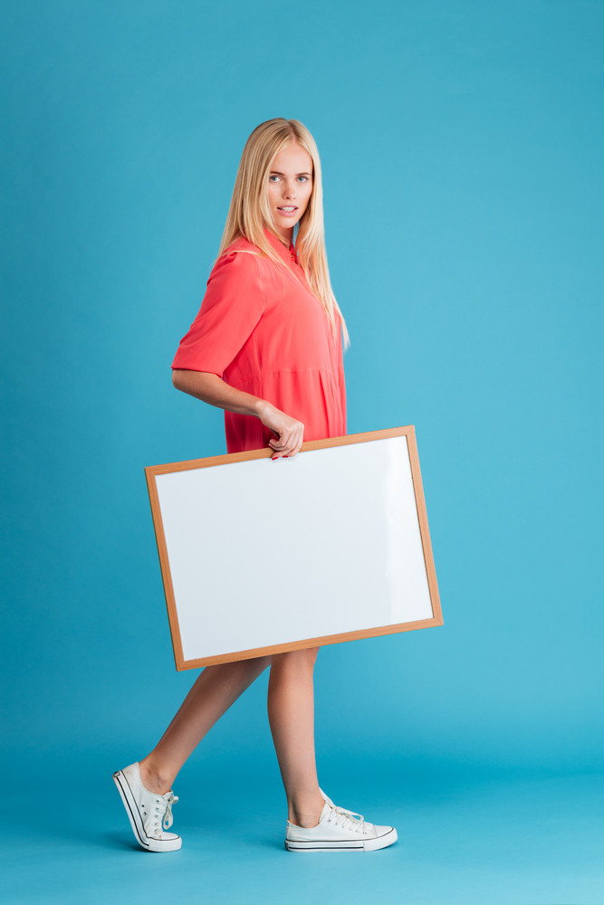 Full length portrait of a smiling beautiful woman holding blank board and looking at camera over blue background