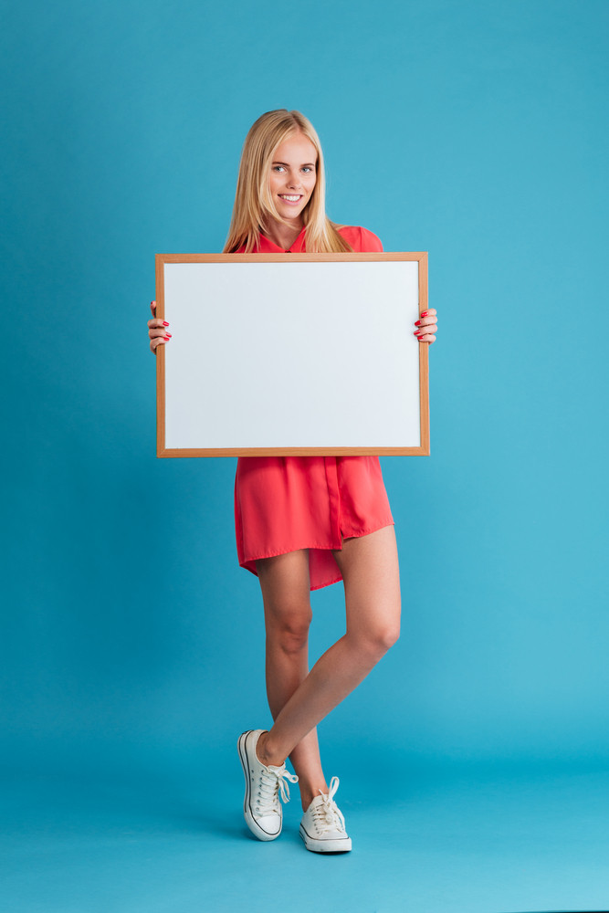 Full length portrait of a smiling blonde woman holding blank board over blue background