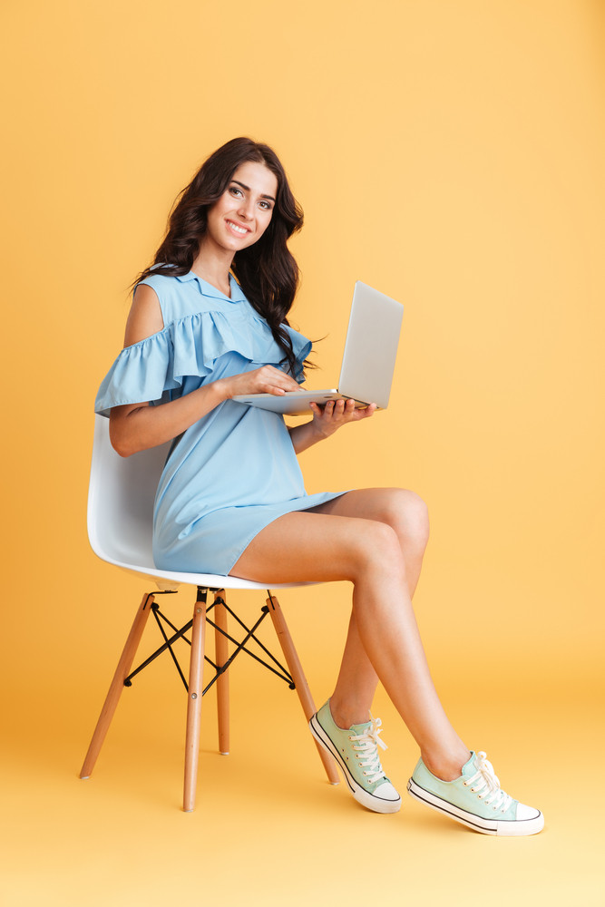 Full length portrait of a smiling brunette woman holding laptop and sitting on chair isolated on the orange background