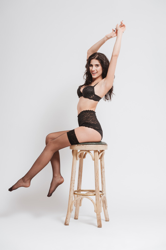 Full length portrait of a smiling brunette woman in lingerie and stockings sitting on a chair and stretching hands isolated on a white background
