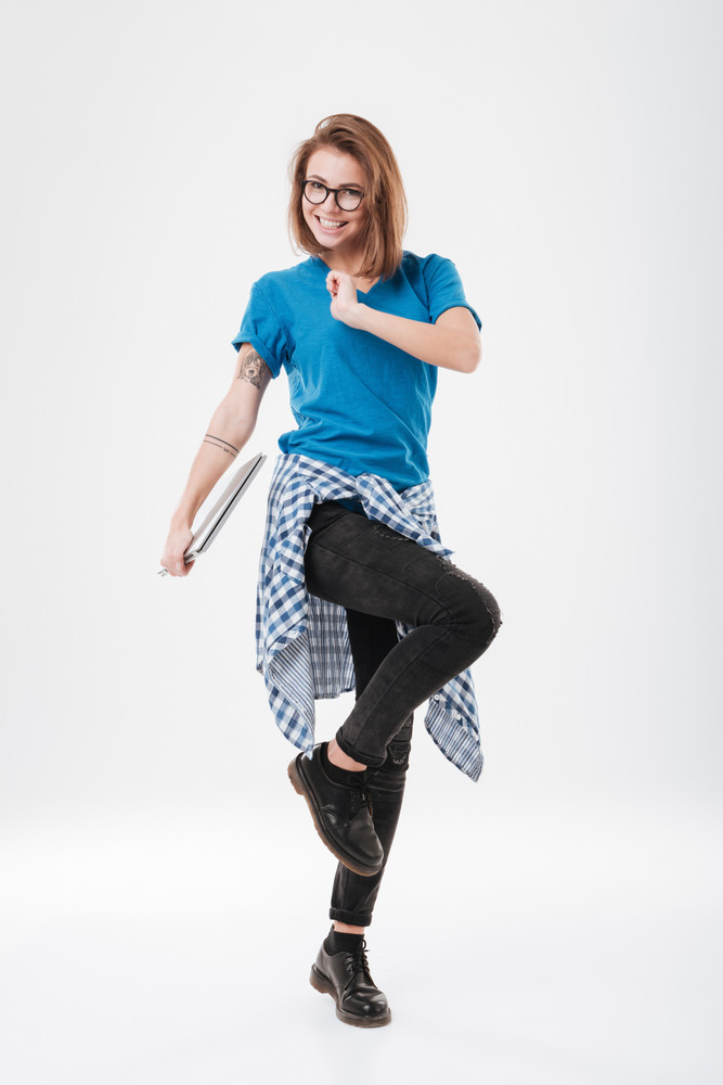 Full length portrait of a smiling casual girl in eyeglasses walking and holding laptop computer isolated on a white background
