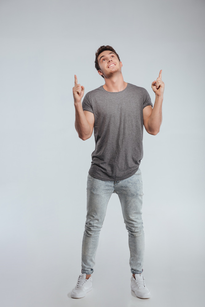 Full length portrait of a smiling casual man pointing fingers up isolated on a white background