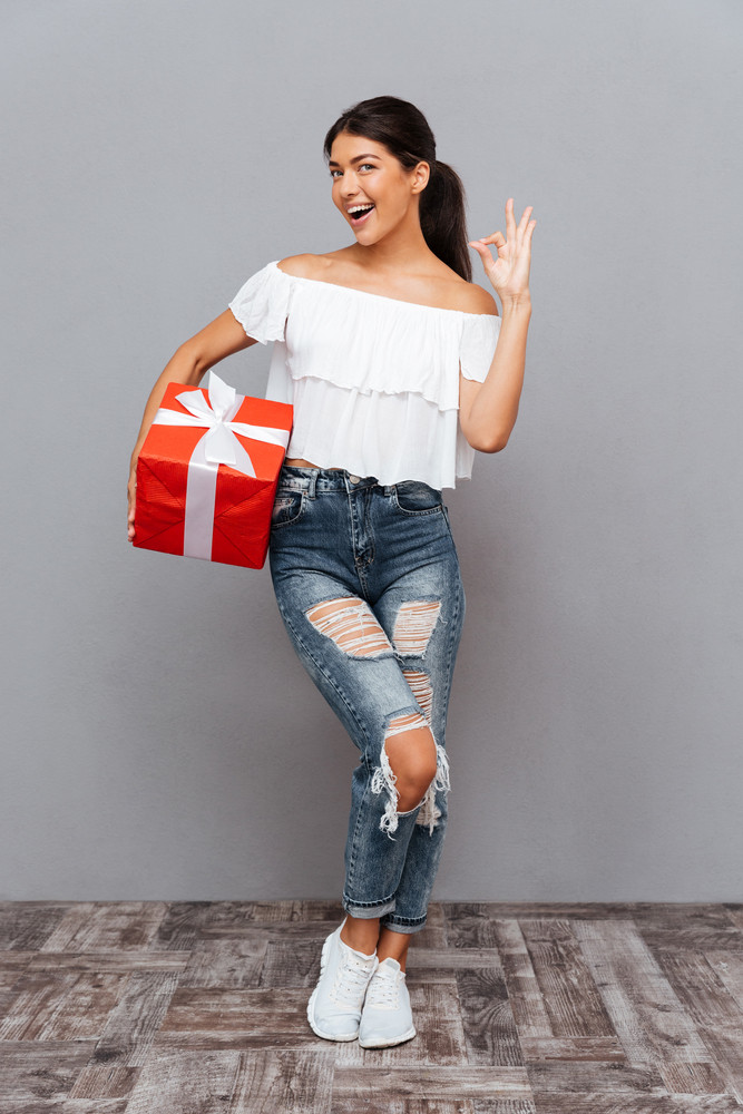 Full length portrait of a smiling casual woman holding gift box and showing okay sign isolated on a gray background