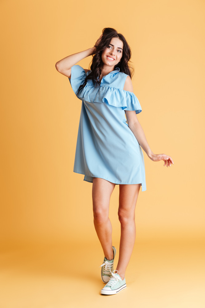 Full length portrait of a smiling cheerful woman posing in blue dress isolated on a orange background