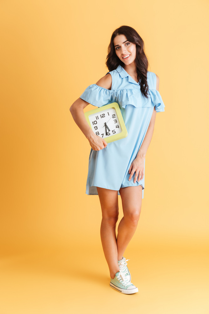 Full length portrait of a smiling happy brunette woman in blue dress holding wall clock isolated on the orange background