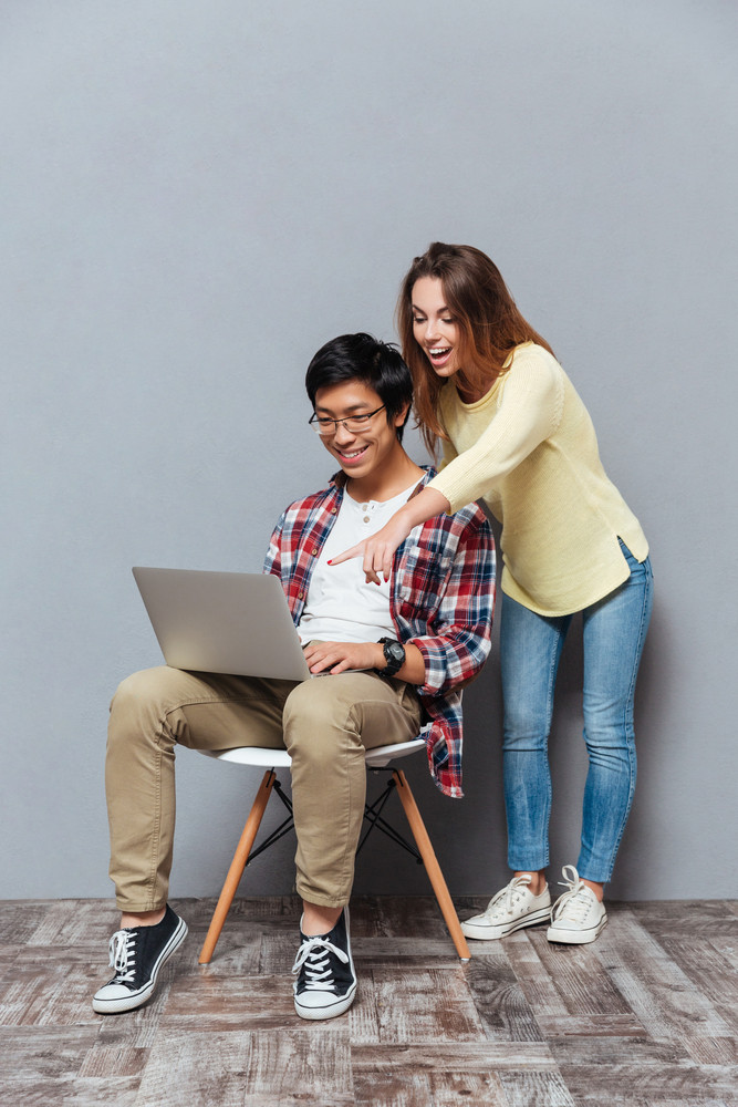 Full length portrait of a smiling multiracial couple using laptop isolated on the gray background