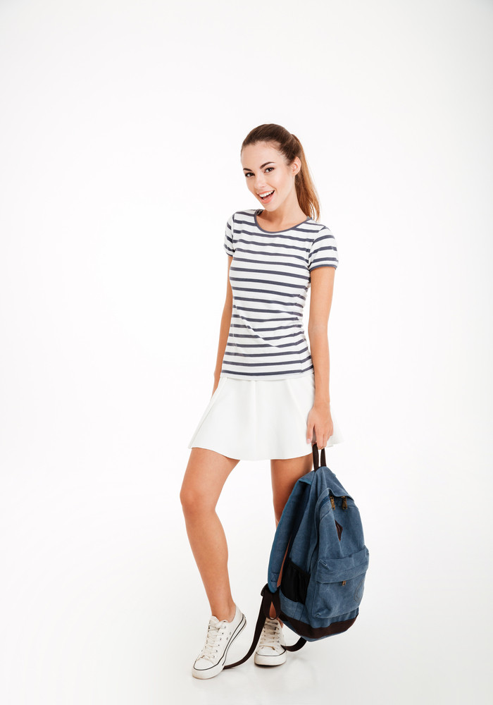Full length portrait of a smiling woman holding backpack isolated on a white background