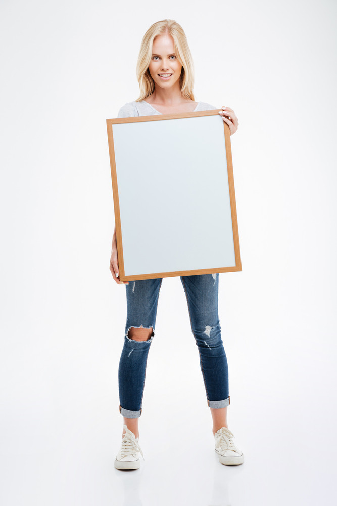Full length portrait of a smiling woman holding blank board isolated on a white background