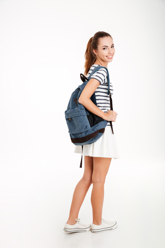 Full length portrait of a smiling woman with backpack standing on white background and looking at camera