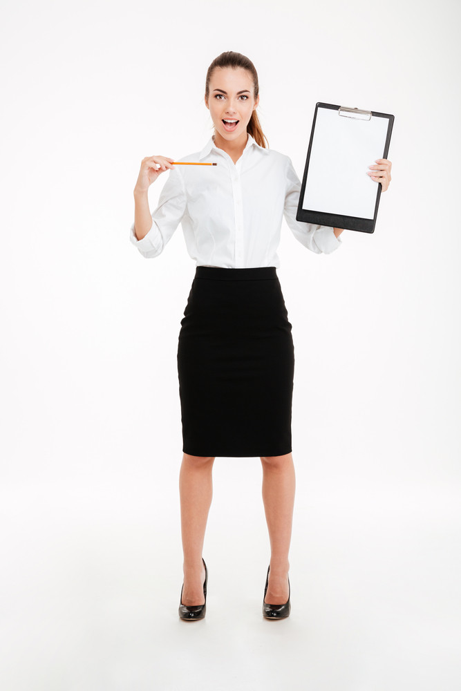 Full length portrait of a smiling young businesswoman pointing pencil at blank clipboard isolated on white background