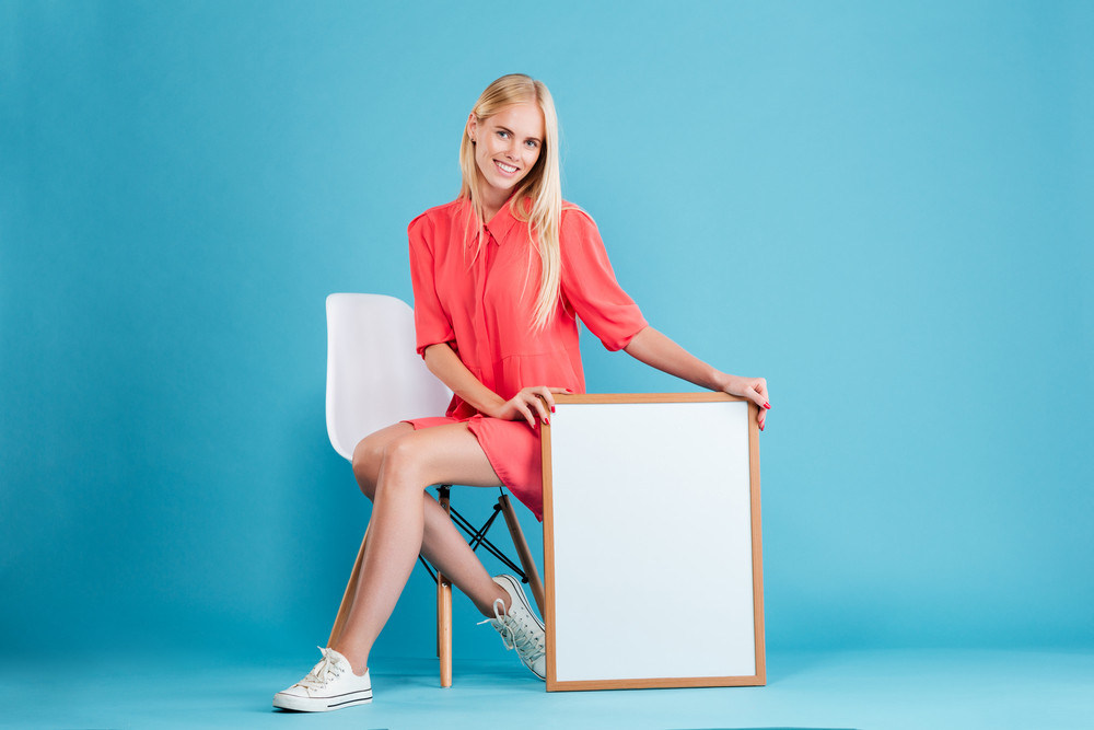Full length portrait of a smiling young woman holding blank board while sitting on the chair isolated on the blue background