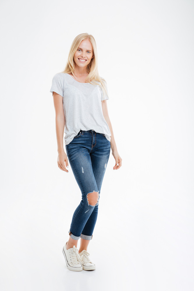 Full length portrait of a smiling young woman standing isolated on a white background