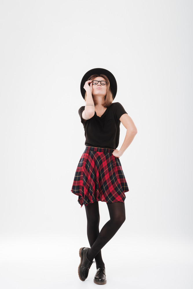 Full length portrait of a stylish young girl in hat standing and posing isolated on the white background
