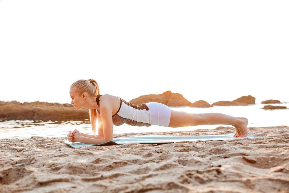 Full length portrait of a young blonde woman doing planking on yoga mat on beach