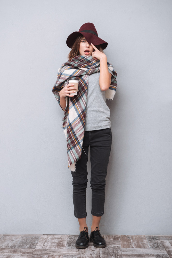 Full length portrait of a young funny woman wearing scarf and hat holding cup of coffee isolated on the gray background