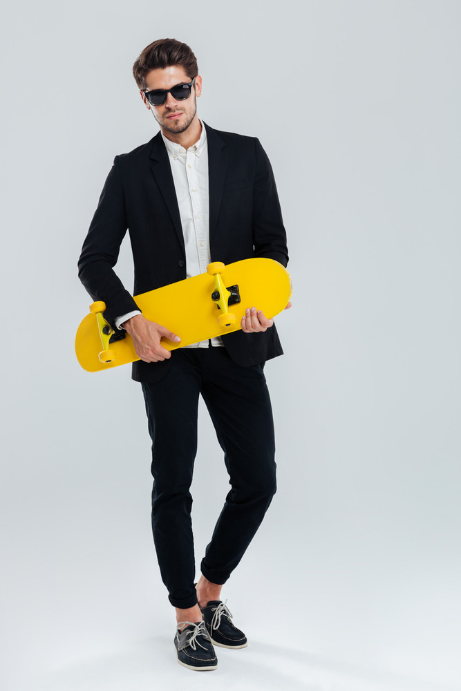 Full length portrait of a young handsome businessman in suit and suglasses holding yellow skateboard over gray background