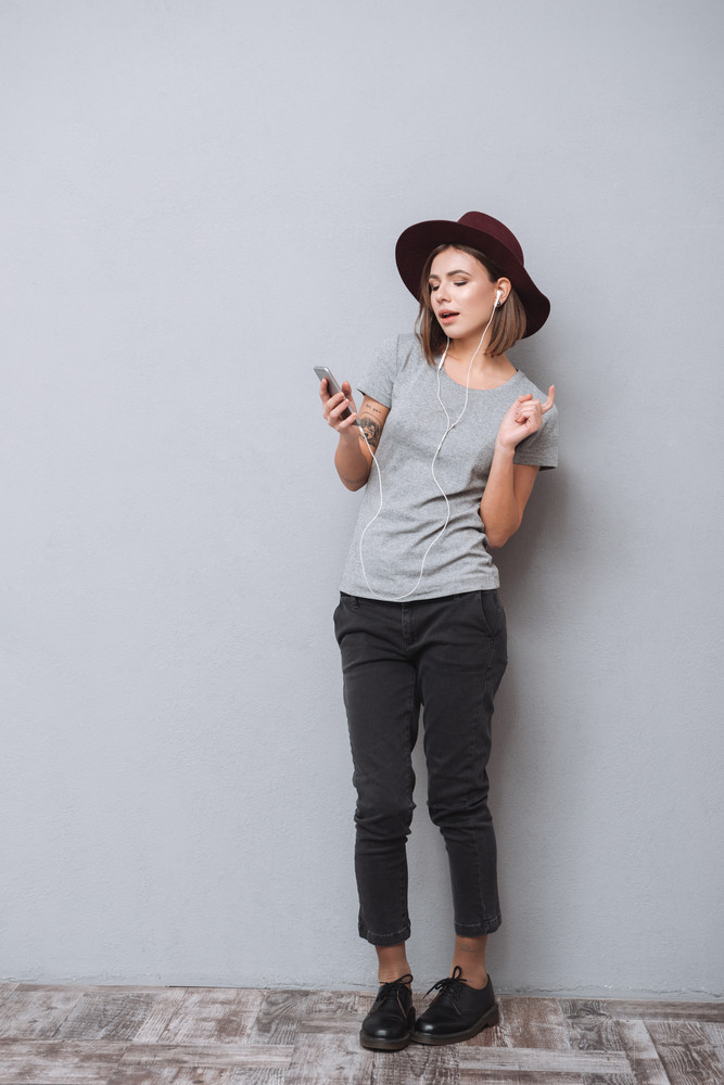 Full length portrait of a young pretty girl in hat listening music and dancing isolated on a gray background
