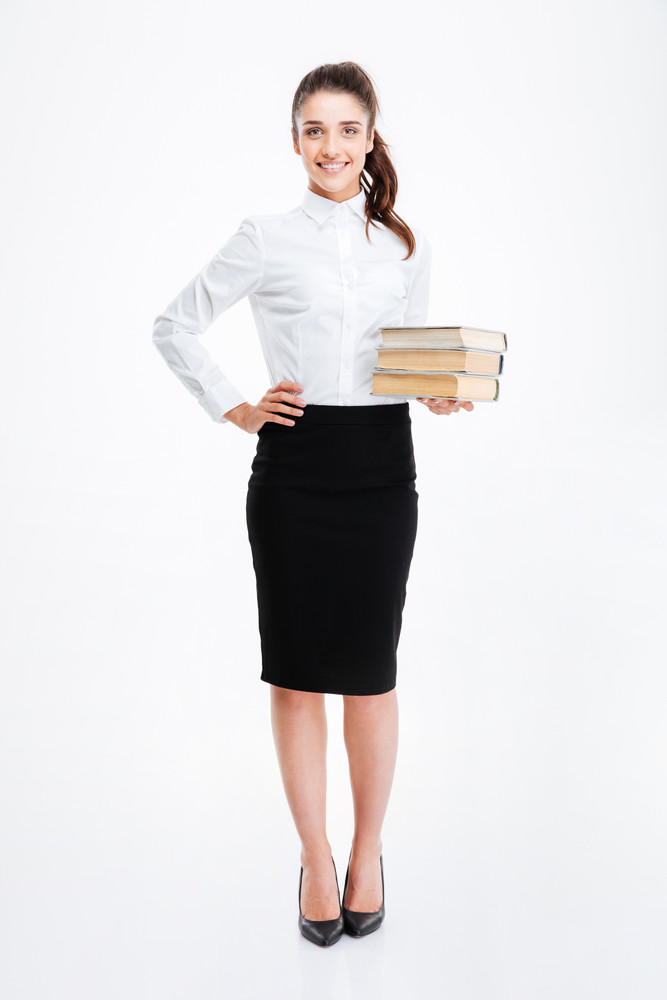 Full length portrait of a young smiling business woman holding books isolated on white background