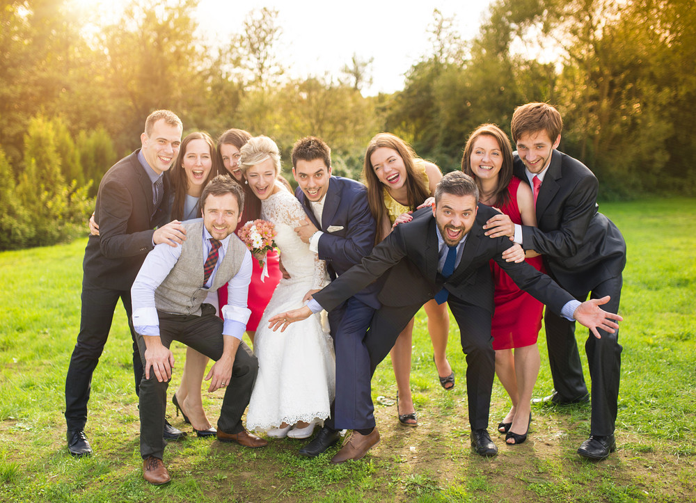 Full length portrait of newlywed couple having fun with bridesmaids and groomsmen in green sunny park