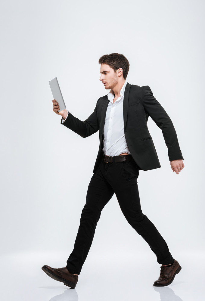 Full length serious businessman in suit walking with tablet computer isolated on a white background