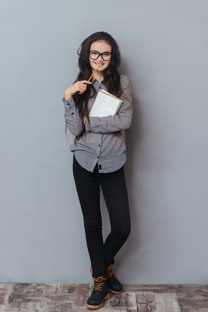 Full length smiling asian woman in glasses and gray shirt holding notebook. Vertical image. Isolated gray background