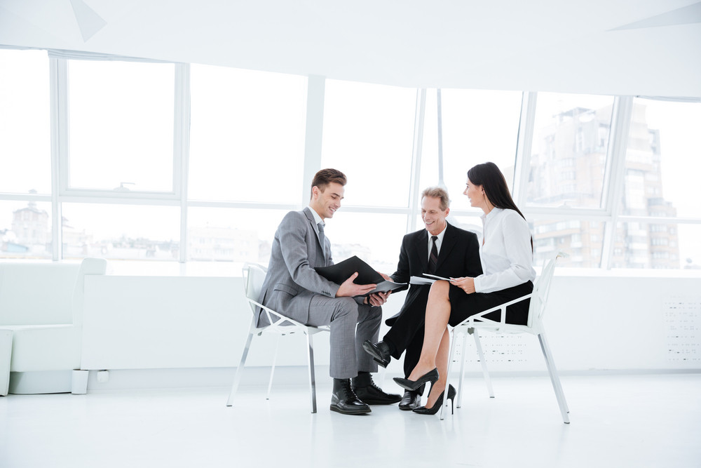 Full length three business people sit on chairs with documents in office