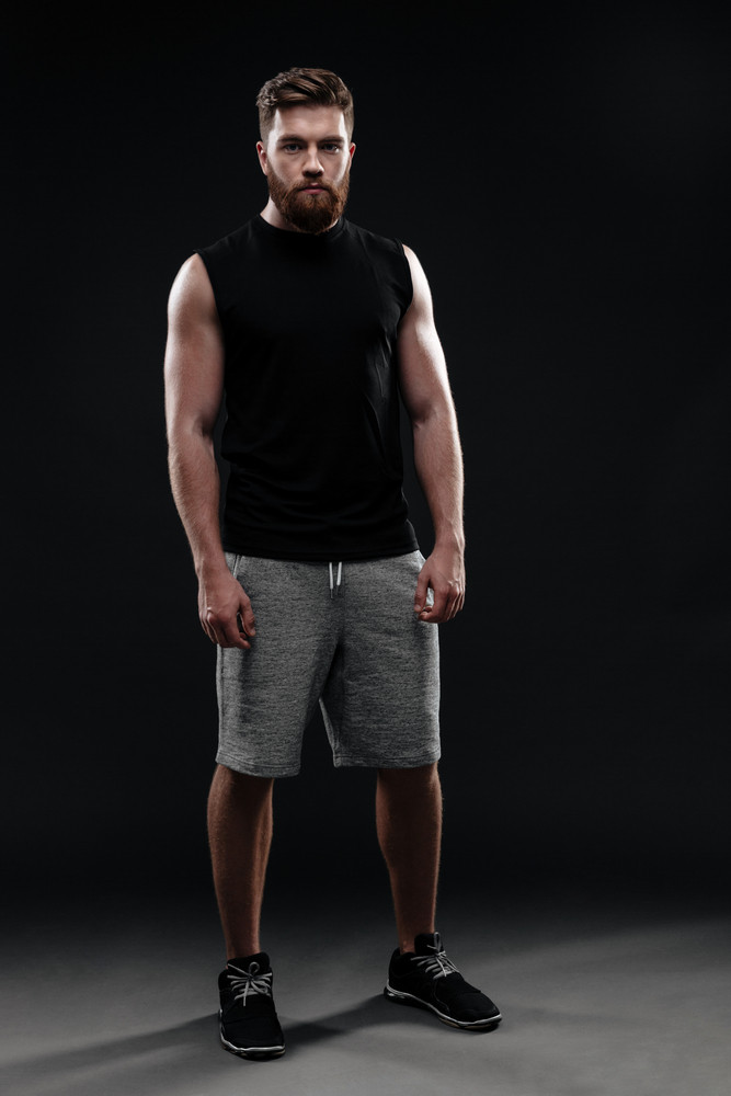 Full length trainer. looking at camera. isolated dark background