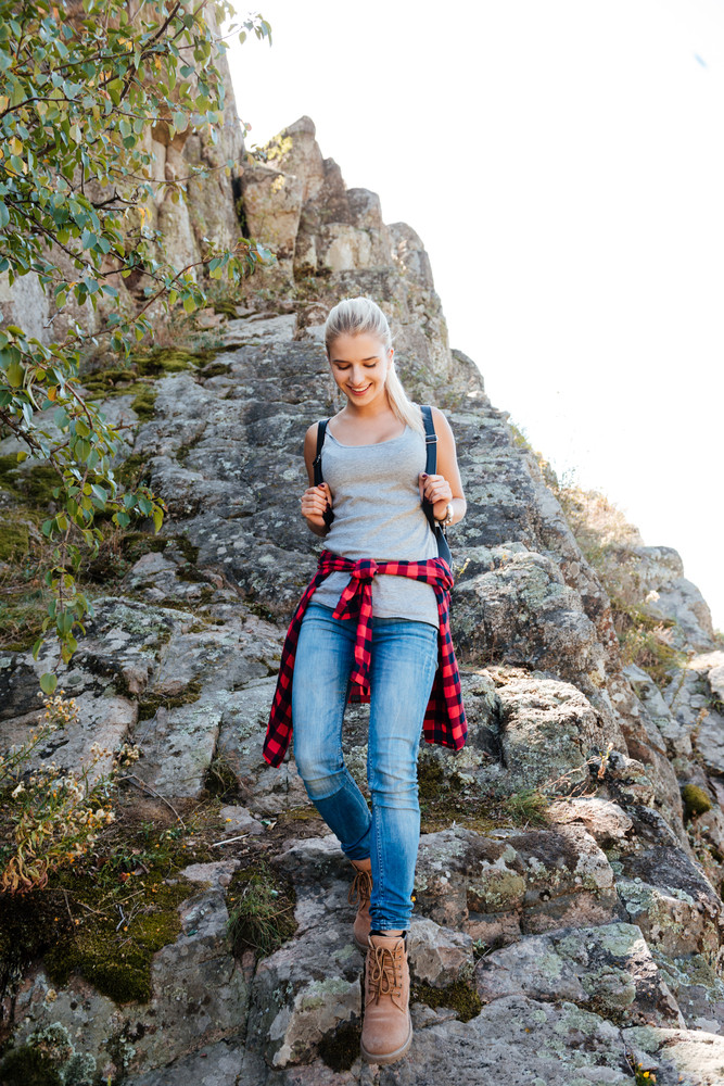 Full length traveling girl with backpack on rock