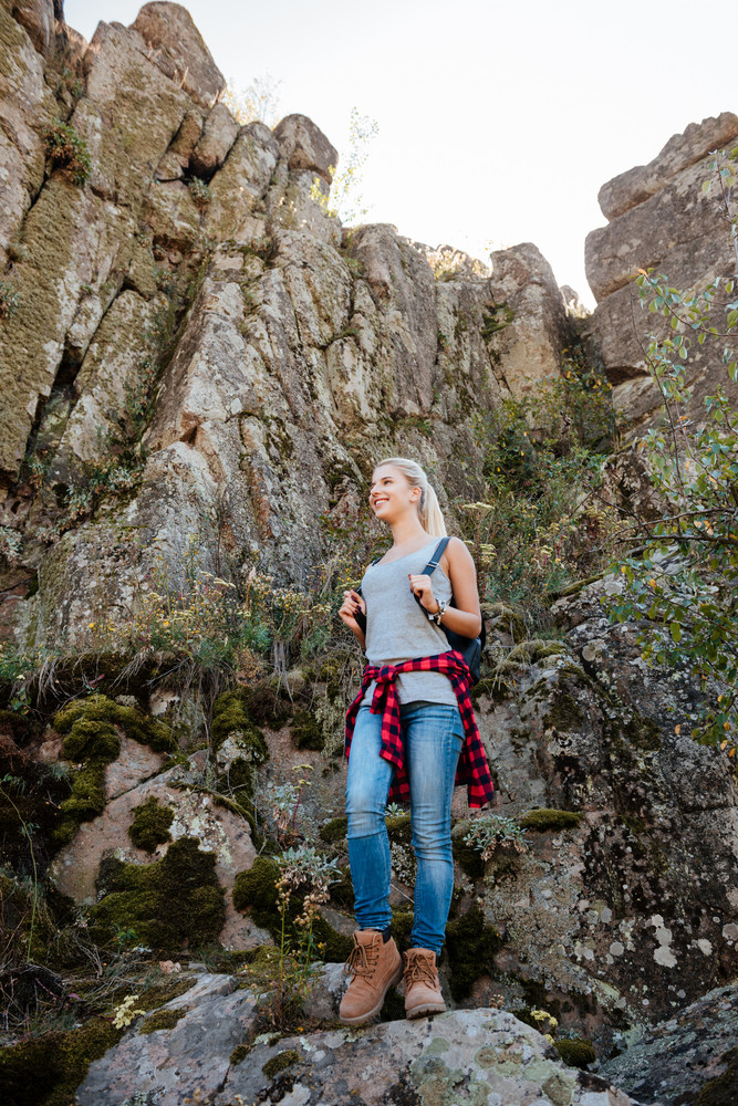 Full length traveling girl with backpack stands on rock and looking away