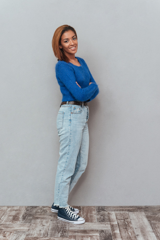 Full length young pretty african woman in sweater and jeans standing sideways with arms crossed looking at camera. Isolated gray background