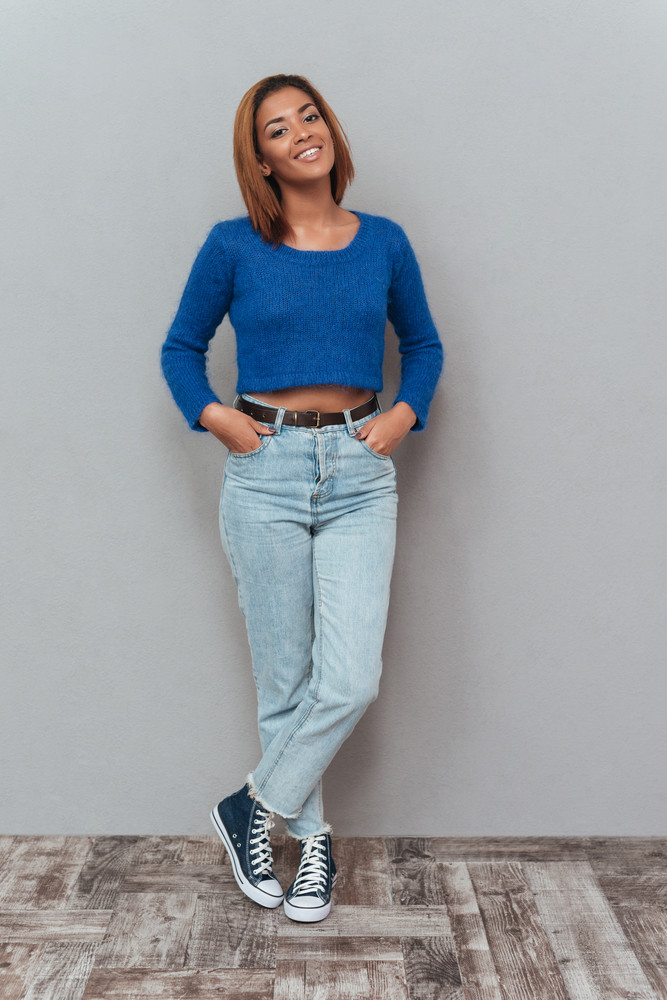 Full length young smiling african woman in sweater and jeans holding her arms in pockets and standing near the wall. Isolated gray background